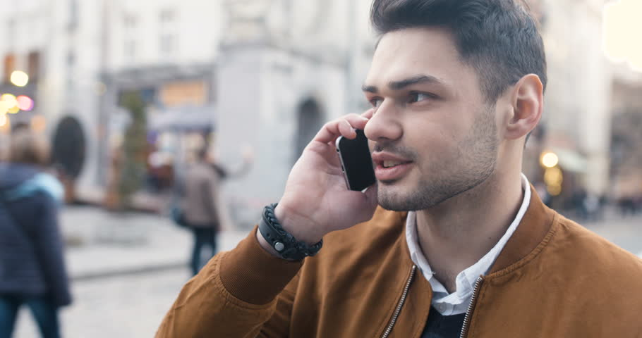 Handsome young man speaking and smiling on a mobile at the street of the big city | Shutterstock HD Video #25089593