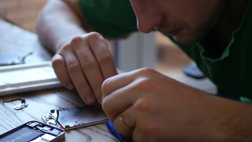 Master repairing broken phone, stares, collects small parts, which are on the table, connects ditali press. 3840x2160. 4k | Shutterstock HD Video #25122725