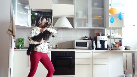 Happy young beautiful woman is dancing in kitchen with her adorable Maine Coon cat wearing headphones in the morning listening to music on smartphone. 3840x2160