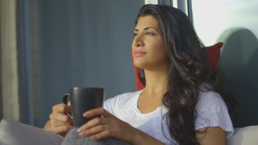 Head and Shoulder shot at a 45 degree angle of a woman sitting on the couch outside in the sun looking out at the view. Continues. | Shutterstock HD Video #25149890