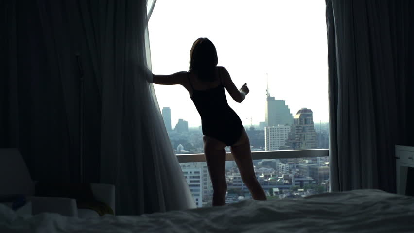 Young, sexy woman unveil curtain and looking from the window, super slow motion