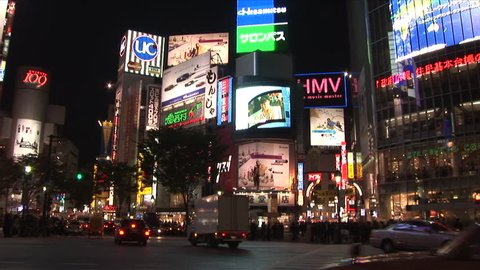 Tokyo, Japan - CIRCA November, 2006: Traffic drives past the camera in a busy intersection with many large billboards during the evening rush hour
