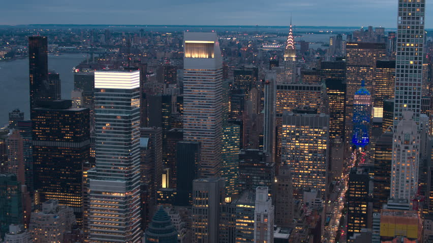 AERIAL NO VISIBLE TRADEMARKS: Iconic Midtown Manhattan skyline lit up against morning sky looking towards downtown financial district. Lights in contemporary skyscrapers turned on and glowing at night | Shutterstock HD Video #25170443