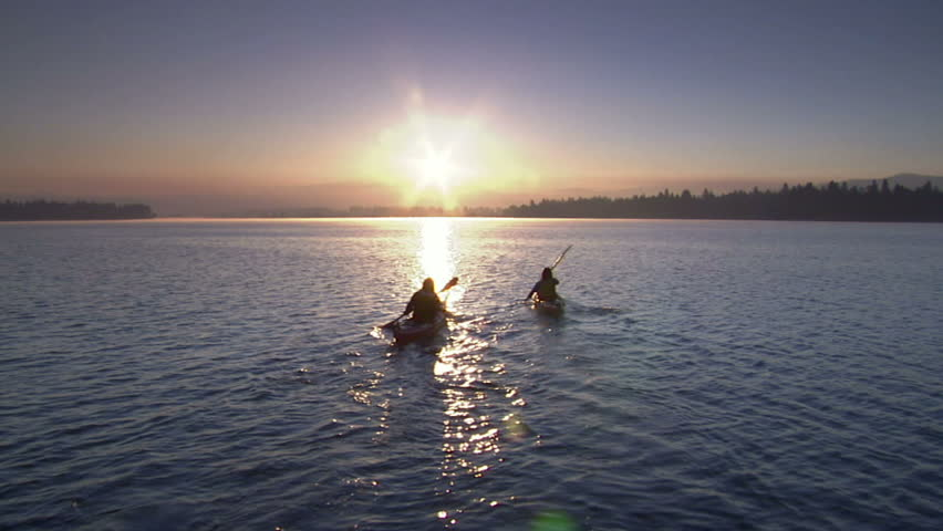 Two women kayak at sunrise on a mountain lake