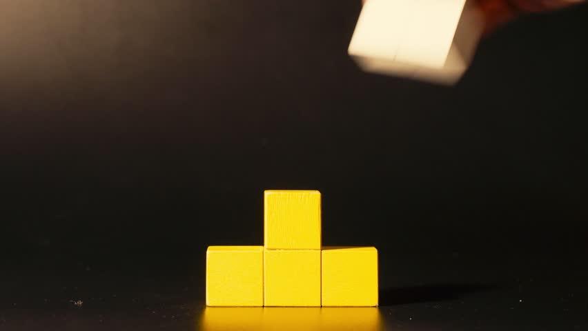 Man's hand picking 3D tetris close up