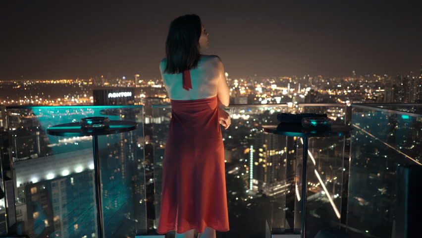Young, elegant woman standing on terrace and admire cityscape at night  | Shutterstock HD Video #25214390