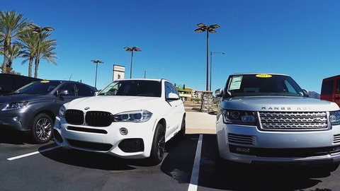 SCOTTSDALE AZ/USA: February 28, 2017- Driving shot by expensive used sport utility vehicles at a dealership. A row of pricey SUVs are lined up for viewing for potential car buyers.