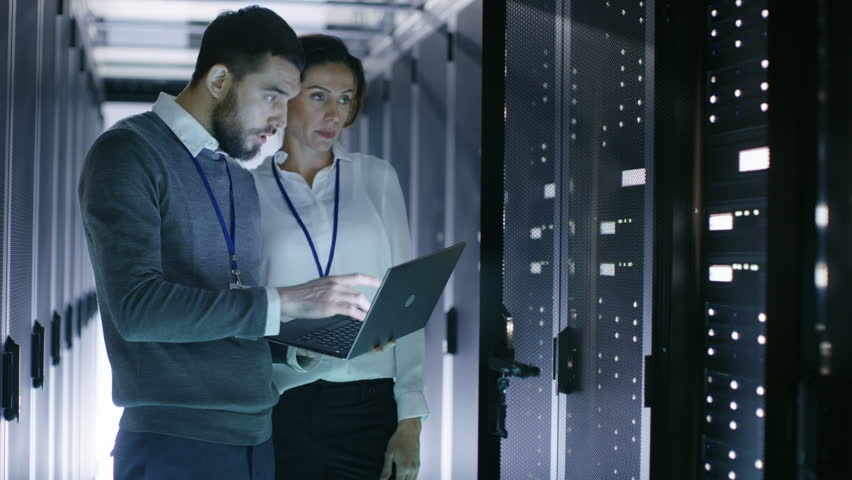 Male and Female Server Engineers Work on a Laptop in Data Center. He Opens Rack Server Cabinet. Shot on RED EPIC-W 8K Helium Cinema Camera.   Shutterstock HD Video #25243076