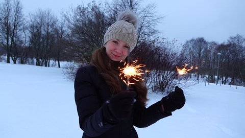 Pretty young woman with sparklers fireworks in two hands pose at winter park, evening twilight, empty snowy field. Coquettish girl look straight to camera, turn and bend, slow motion shot from 120 fps