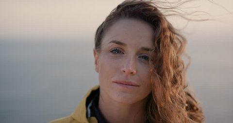 Close up portrait of Young Woman smiling with Red hair blowing in wind looking at sunset over ocean Girl wearing yellow raincoat trekking in Scotland Slow Motion