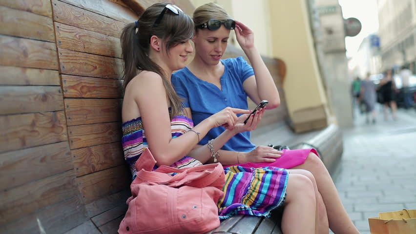 Female friends with smartphone in the city