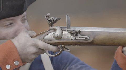 VIRGINIA - OCTOBER 2016 - American Revolution era Continental Patriot Soldier. Re-enactors, reenactment.  Firing Brown Bess musket gun with black powder and lead bullets in earthen fort in battle.
