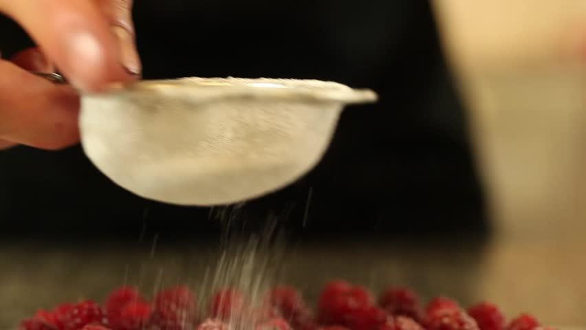 sugar falls on raspberry tart