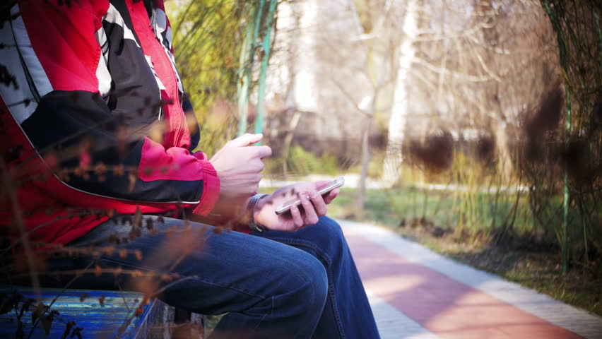 Young Man using a Mobile Phone on a Bench in the City Park. A man holds a smartphone in his hands and controls his finger gestures and looks at social networks.   Shutterstock HD Video #25320989
