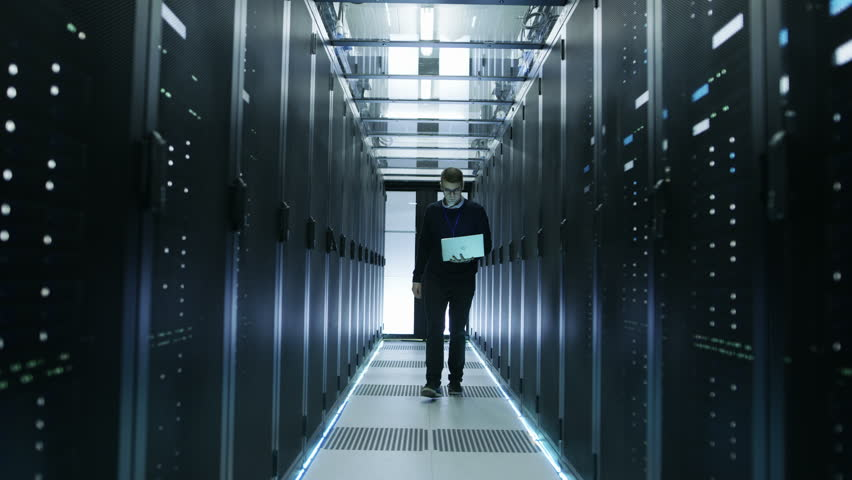 Frontal View of IT Engineer Walking Through Data Center full of Working Rack Servers. He Opens Server Cabinet and Connects to it With His Laptop. Shot on RED EPIC-W 8K Helium Cinema Camera. #25323380