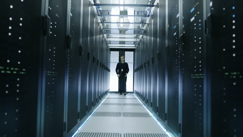 Frontal View of IT Engineer Walking Through Data Center with Working Rack Servers. Shot on RED EPIC-W 8K Helium Cinema Camera. #25323410