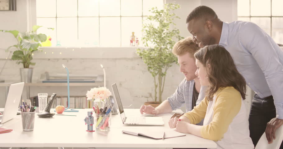 Track across table in casual sunny startup office with young happy adults. Raw version available on request. | Shutterstock HD Video #25328360