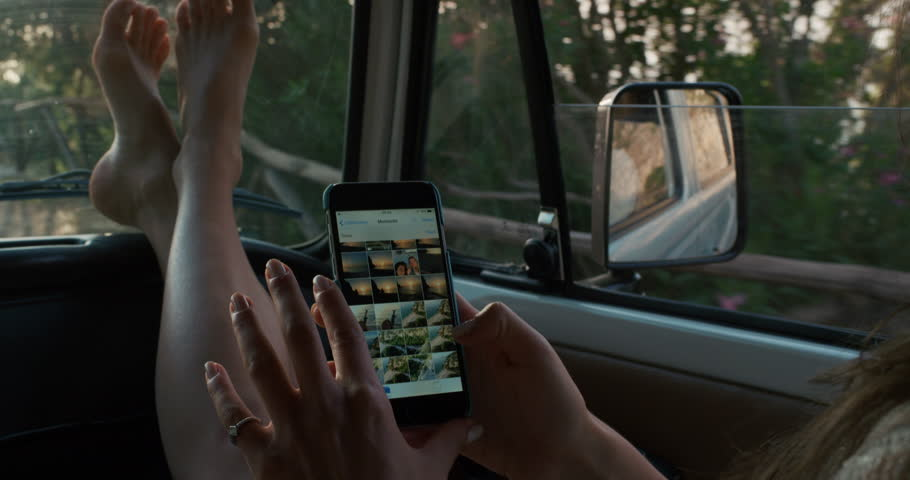 Close crop Woman using smartphone browsing social media on mobile phone connecting with friends driving in car on road trip adventure enjoying a relaxing summer vacation