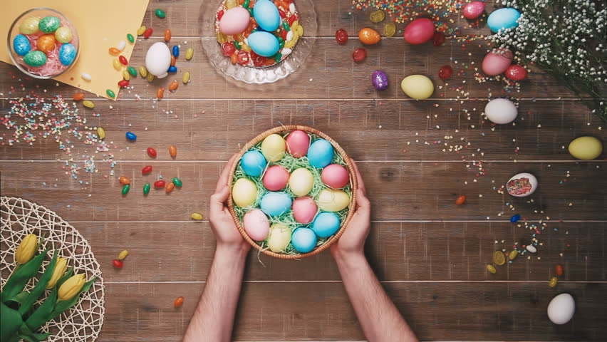 Man taking basket with easter egg from the table decorated with easter eggs. Top view | Shutterstock HD Video #25342940