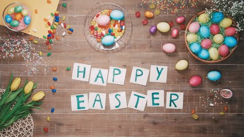 Man put words Happy Easter on table decorated with easter eggs. Top view
