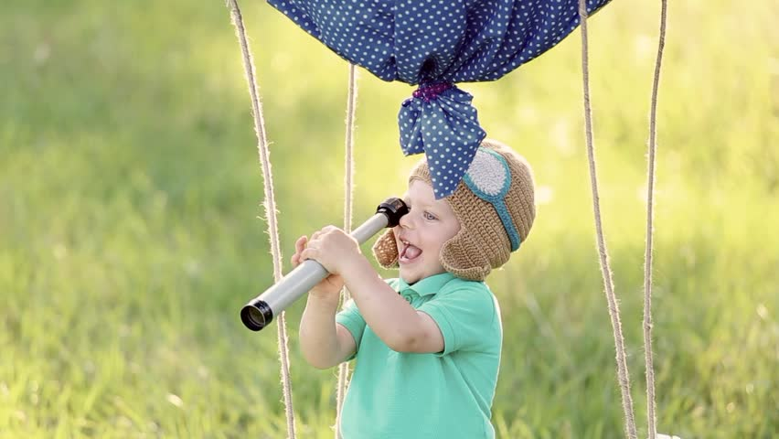 Beautiful funny little child wearing knitted pilot hat plays in handmade toy airballoon at nature background. Laughing baby holds telescope in hands and looks through it. Real time full hd video.