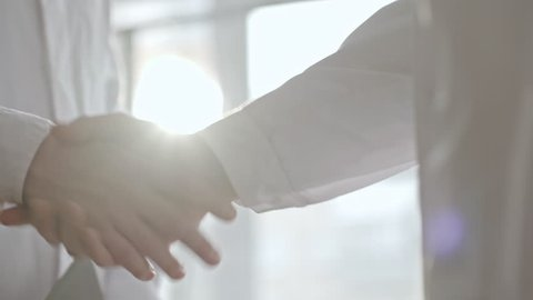 Mid-section shot with PAN of male doctors in lab coats greeting each other with handshake and discussing patient file on clipboard