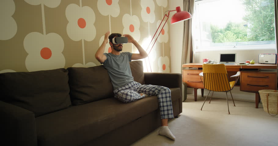 Young Man wearing virtual reality headset sitting on sofa at home watching 360 video imagination concept in retro styled modern apartment | Shutterstock HD Video #25399010