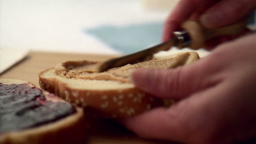 Woman making peanut butter and jelly sandwich