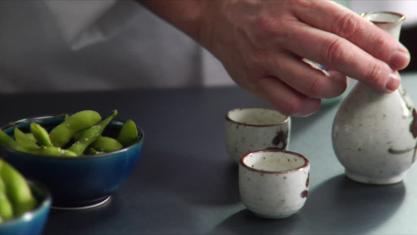 Close-up of chef pouring hot sake with bowls of Edamame (soy beans) on the side.