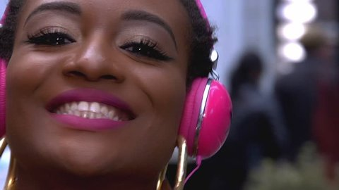 Young African American Woman Listening To Pink Vintage Headphones While Dancing in Times Square New York City