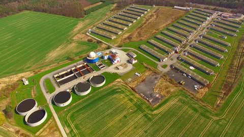 Camera flight over biogas plant from pig farm. Renewable energy from biomass. Modern agriculture in Czech Republic and European Union.
