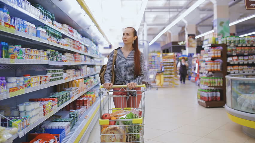A woman in a supermarket is passing by the basket past the counters | Shutterstock HD Video #25471403
