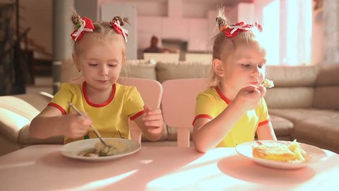 Two little cute twin sisters in yellow T-shirts are eating food together at the table in the kitchen of the house.