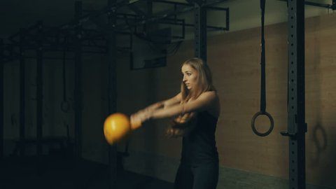 Beautiful young woman training with kettlebell weight in gym. Locked down real time 4K video.