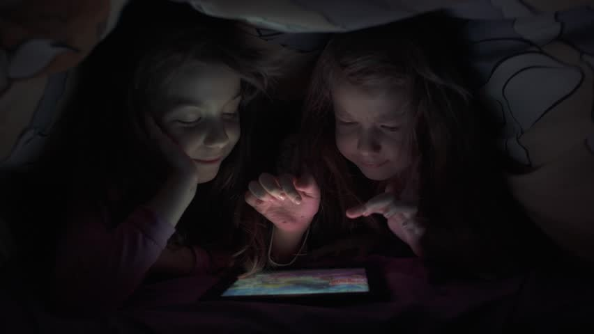 Children play on a tablet computer at night, hiding from their parents under the blanket