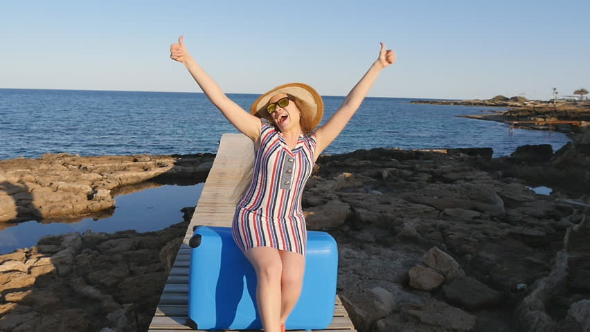 Happy young woman on vacation with a suitcase | Shutterstock HD Video #25498730