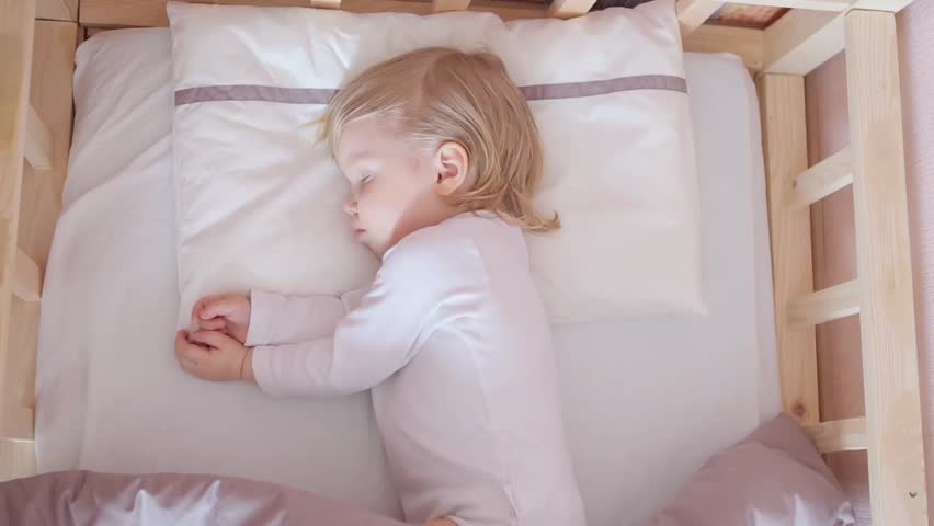Peaceful adorable baby sleeping on his bed in a room. Soft focus. Mum covers the sleeping child with a blanket. Sleeping baby concept. 2 years-old babyboy sleeps at home, top view