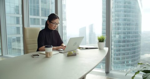 closeup Asian girl in a modern office, business correspondence using a laptop