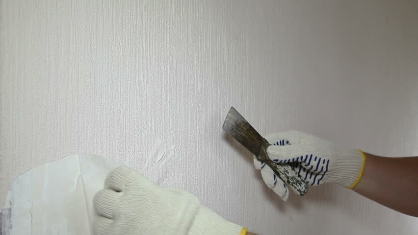Man Removing Old Wallpaper With The Tool