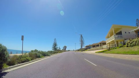 Vehicle POV, driving along the scenic Esplanade, with views of beach and ocean on sunny day, in the coastal suburb of  Moana in Adelaide, South Australia.