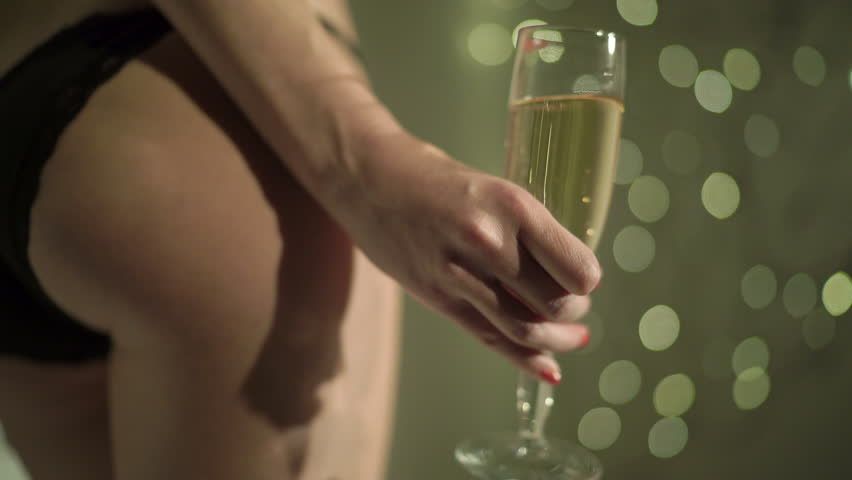 Sexy woman in black panties holding champagne glass over holiday glowing highlights background | Shutterstock HD Video #25597160