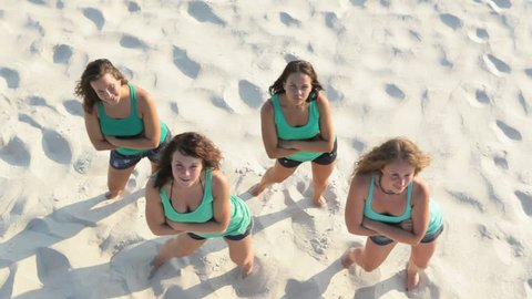 Above view of pretty girls dancing on the sand
