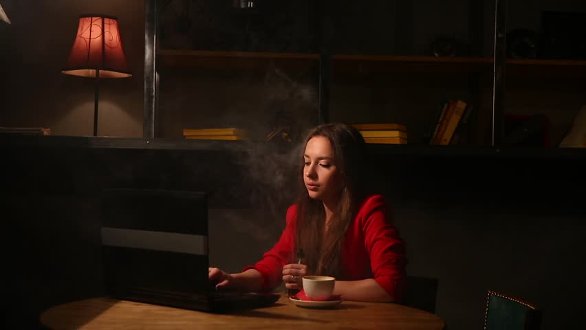 Girl working with laptop drinking coffee Smoking an electronic cigarette. Working remotely in a cafe. | Shutterstock HD Video #25627400