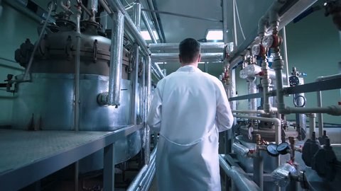 Rear view video of unrecognizable male scientist in white uniform walking through lad with metal tubes and engineering equipment aside