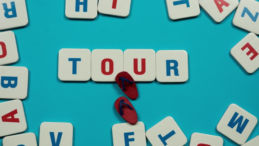 Word tour formed of blue and red letters on the skyblue background. Red flip flops walks on text. Stop motion