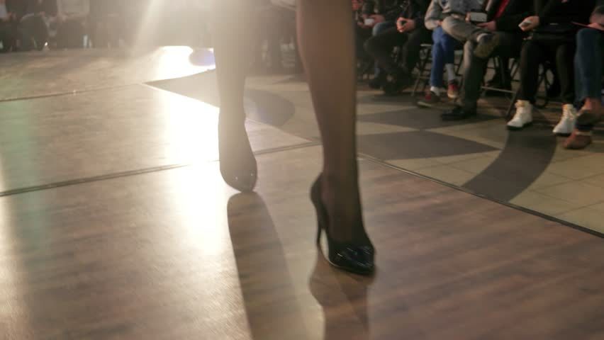 model walking runway, girls legs walking down catwalk closeup, demonstration of black leather shoes on fashion show, woman demonstrating shoes on high heels, show on catwalk, professional model defile