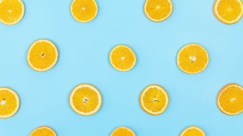 Fruits Are Dancing. Stop Motion Animation With Oranges and Kiwi on a Blue Background. Top View. 4K.