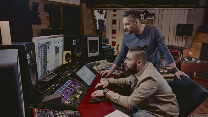 Sound engineer and musicians working in boutique recording studio.