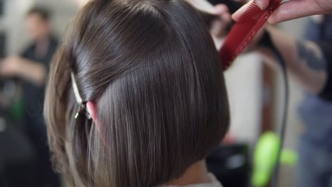 Professional hairdresser, stylist makes professional hairstyle of young woman in beauty studio, using barrette for fixing hairdo. Hair straightening Beauty and haircare concept