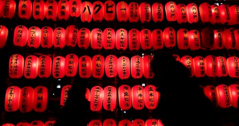 Silhouette of people walking in the night with red lanterns background. Tokyo, Japan.